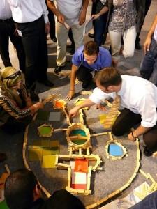 Des participants de toutes nationalités échangent sur leur conception d'une maison des ancêtres, puis la construisent